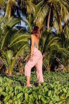 ピンクのズボンと緑の流行のクロップトップで入れ墨の白人女性
