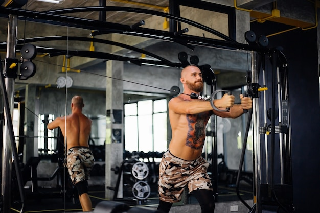 Tattooed fit man doing exercise at the gym