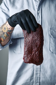 Tattooed hand in black glove holds piece of luxury steak in air