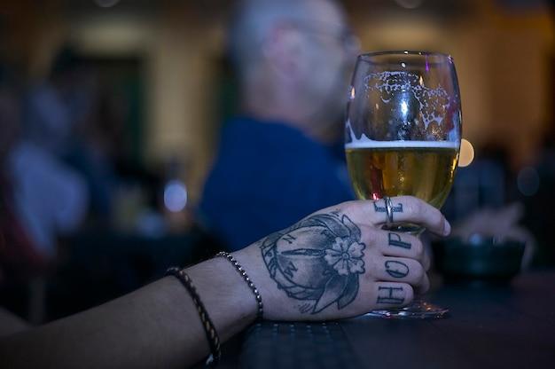 Татуированная рука, держащая стакан пива за столом в баре в ночи.