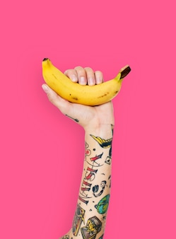 Mano tatuata che tiene una banana