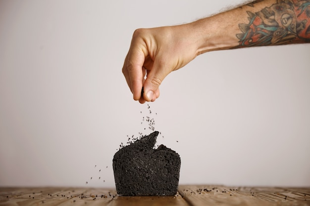 Tattooed hand pours black seeds spices on top of black coal organic homemade bread isolated on craft paper on wooden table in artisan bakery