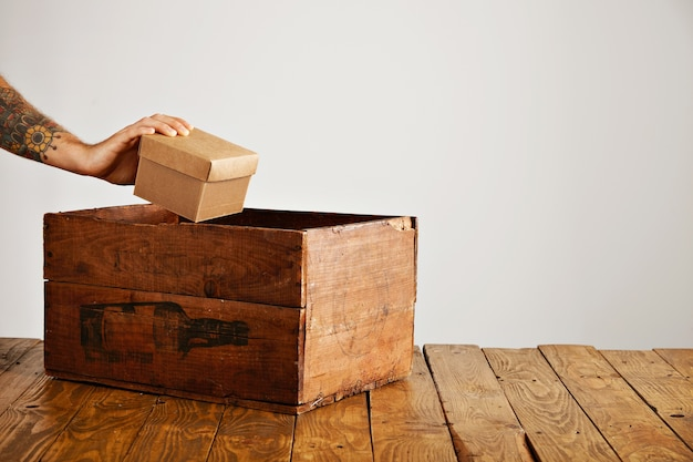 문신을 한 손은 소박한 테이블에 ld 나무 상자 안에 선물로 빈 골판지 패키지를 넣습니다.