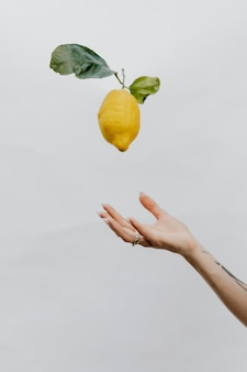 Tattooed hand throwing a lemon up in a gray sky