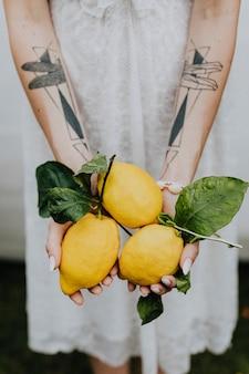 新鮮なレモンを保持している入れ墨の手