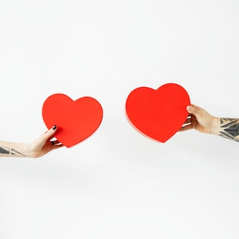 Tattooed hands holding red hearts social ads template