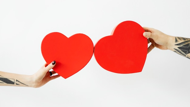 Tattooed hands holding red hearts wallpaper