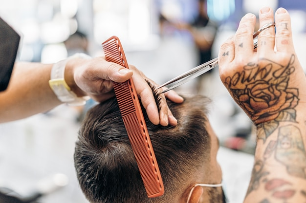 이발소에서 마스크를 쓴 고객의 머리를 자르는 이발사의 문신을 한 손