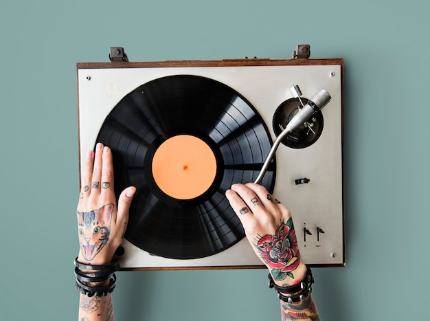 Tattooed hands playing on a vinyl turntable