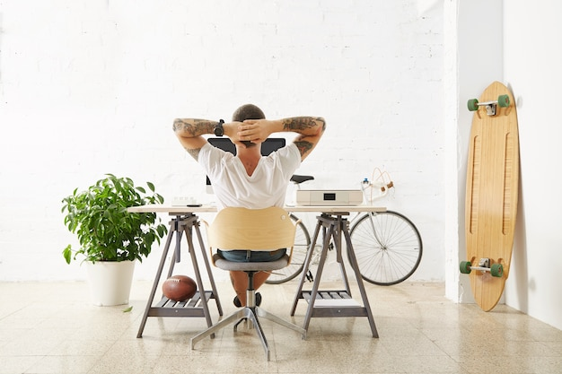 Tattooed man in blank white t-shirt looks in monitor with his hands folded behind head back view in big loft room with brick wall and longboard, rugby ball, green plant and vintage bicycle around him