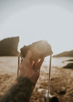 ビーチでコンパクトカメラを保持している入れ墨の男
