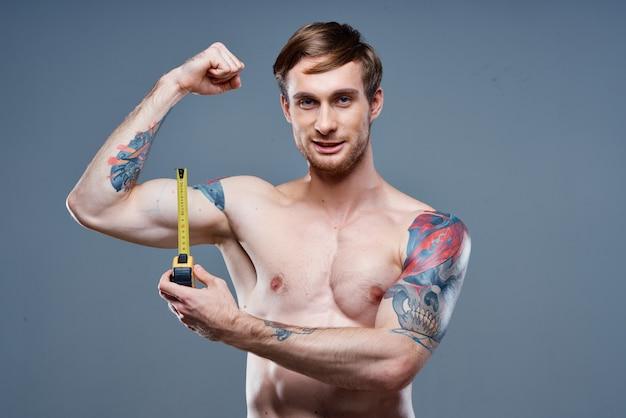 入れ墨の男筋肉ボディービルダーフィットネス灰色の背景
