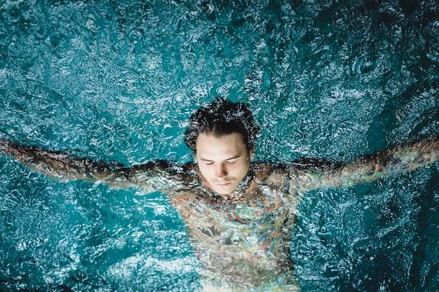 Tattooed man in the pool in the rain.