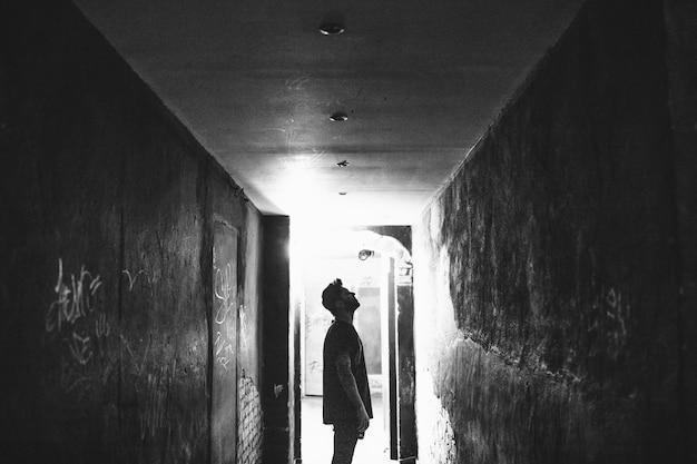Татуированный мужчина смотрит на стены в темном переулке