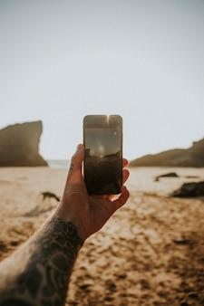 해변에서 휴대전화 카메라를 사용하는 문신을 한 남자