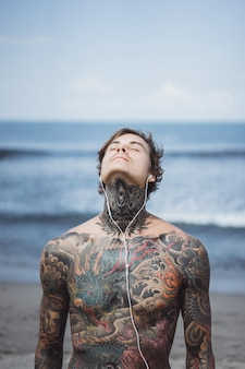 Tattooed man with headphones against the blue sky on the ocean