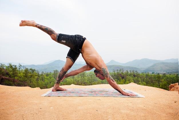 Tattooed man yoga outdoors concept