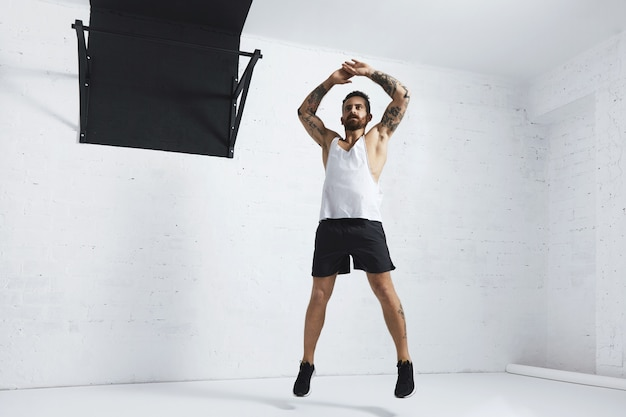Tattooed and muscular athlete doing jumping jacks isolated on white brick wall next to black pull bar