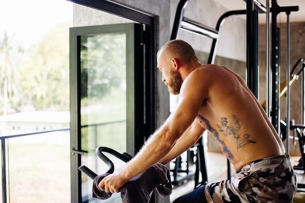 入れ墨された筋肉の強いひげを生やした男は、外の木々の景色を望む大きな窓の近くのジムで自転車で有酸素運動を行います