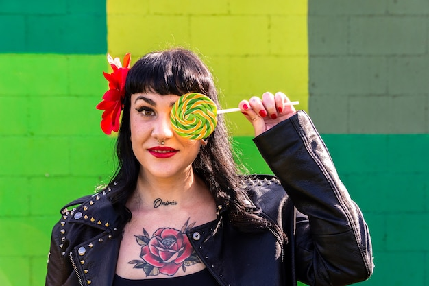 Tattooed rocker woman in leather jacket,   and flower in hair on green wall   covering one eye with a giant lollipop.