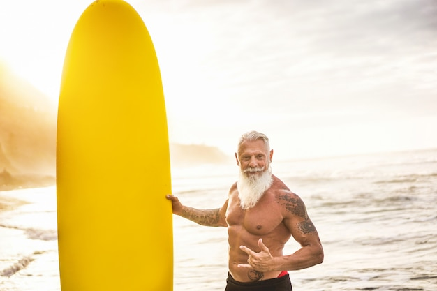 Tattooed senior surfer holding surf board on the beach at sunset