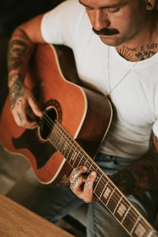 Tattooed singer songwriter playing an acoustic guitar