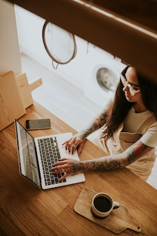 Tattooed small business owner working at home
