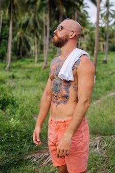 Uomo forte tatuato sul campo tropicale della giungla senza camicia