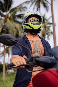 赤いバイクで熱帯のジャングルフィールドに入れ墨の強い男