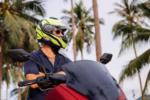 Татуированный сильный мужчина на поле тропических джунглей с красным мотоциклом
