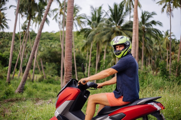 빨간 오토바이와 열 대 정글 필드에 문신 된 강한 남자