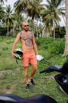 Uomo forte tatuato sul campo della giungla tropicale con una moto rossa