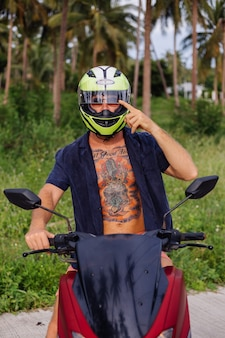 Tattooed strong man on tropical jungle field with red motorbike