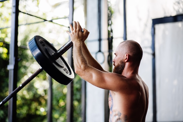 Tattooed strong man with a beard in the gym