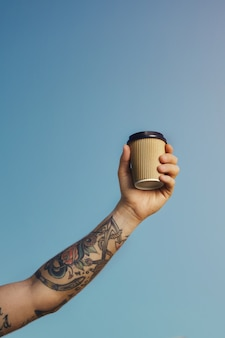 Tattooed white man holds a beige disposable coffee cup high against the clear blue sky