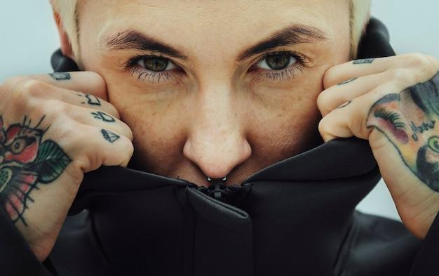 검은 까마귀로 얼굴을 덮고 있는 문신을 한 여성