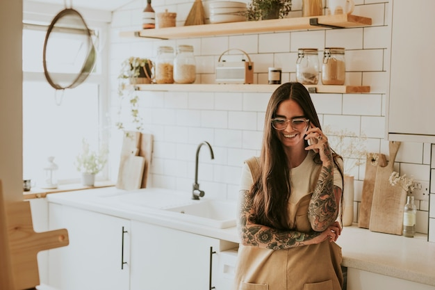 Tattooed woman in kitchen in a phone call