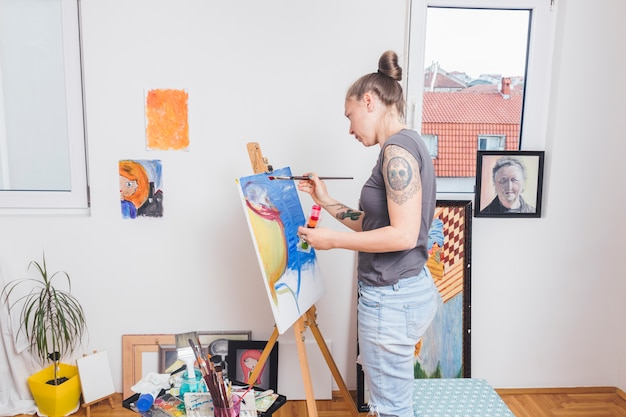 Tattooed woman painting colorful picture standing by window