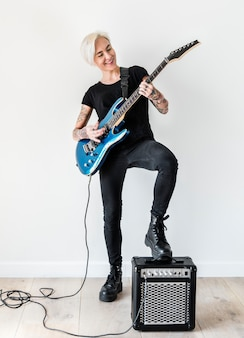 Tattooed woman playing electric guitar