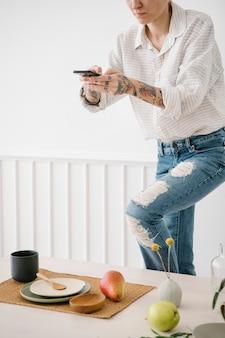 Татуированная женщина фотографирует минимальный набор посуды