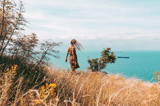 海の旅行と休暇のライフスタイルで金髪のdreadlocksatと入れ墨の女性