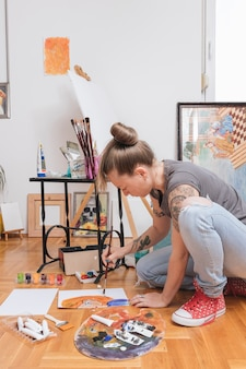 Tattooed young female artist painting picture sitting on floor