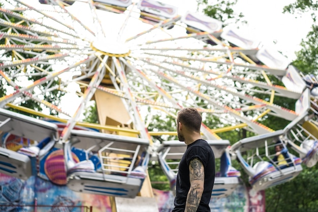 Tattooed young man in an amusement park on the background of a merry-go-round
