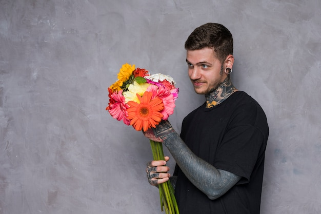 Tattooed young man looking at colorful gerbera flower bouquet standing against grey wall