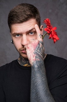 Tattooed young man raising his eyebrow holding red gerbera flower in hand