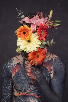 Tattooed young man with pierced ear and nose holding flower bouquet in front of his face