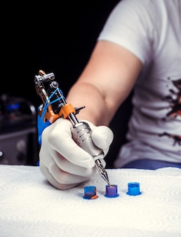 A tattooer, holding in his hand, a tattoo machine.