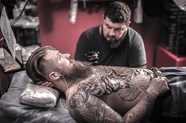 Татуировщик делает рисунки тату в тату студии