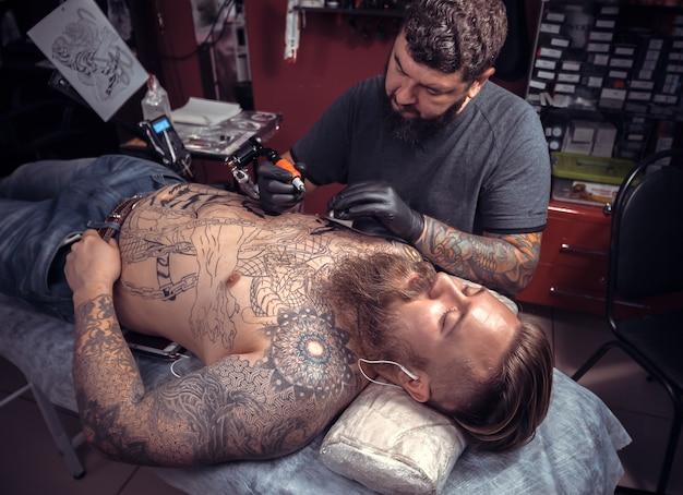 Татуировщик делает татуировку в салоне тату-салона