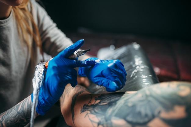 Татуировщик делает татуировку на машине на мужском плече